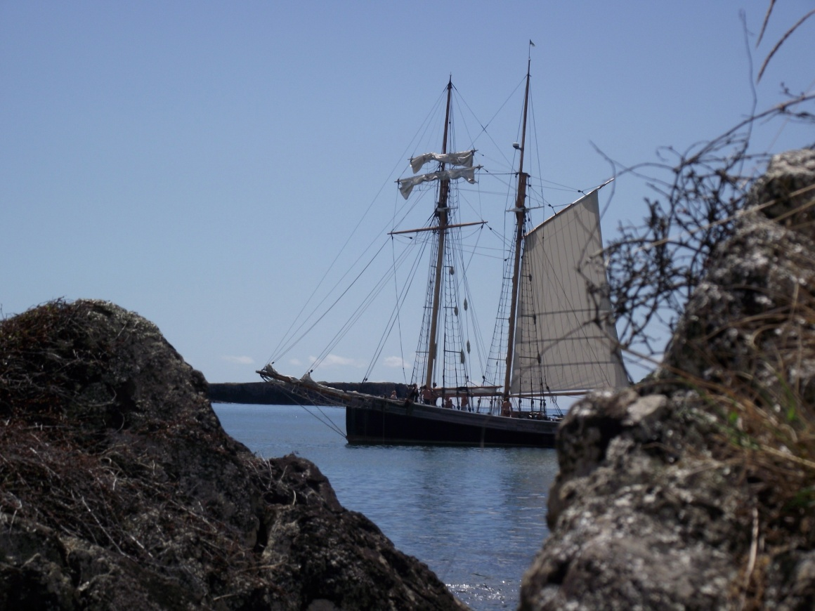 R. Tucker Thompson at anchor.  Partially obscured by out of focus rocks because that is what they do in sailing ship movies when someone is waiting in ambush or hiding from the French.© Lemuel Lyes 2013
