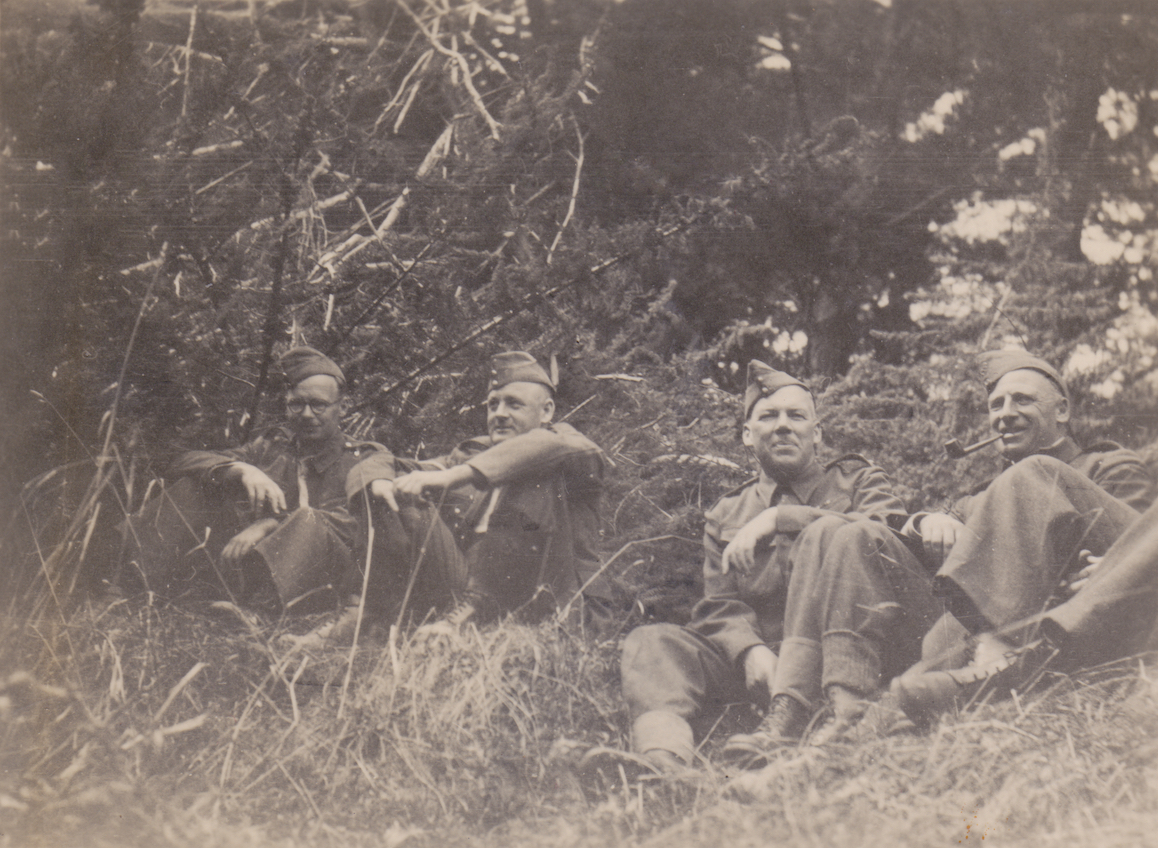 Four members of No. 11 Platoon, Makara Battalion, New Zealand Home Guard, taking a break at Makara, 1942. From L to R they are Elice, Maris, Lieutenant Richards and smoking the pipe is Sergeant Milwood. Lemuel Lyes Collection.