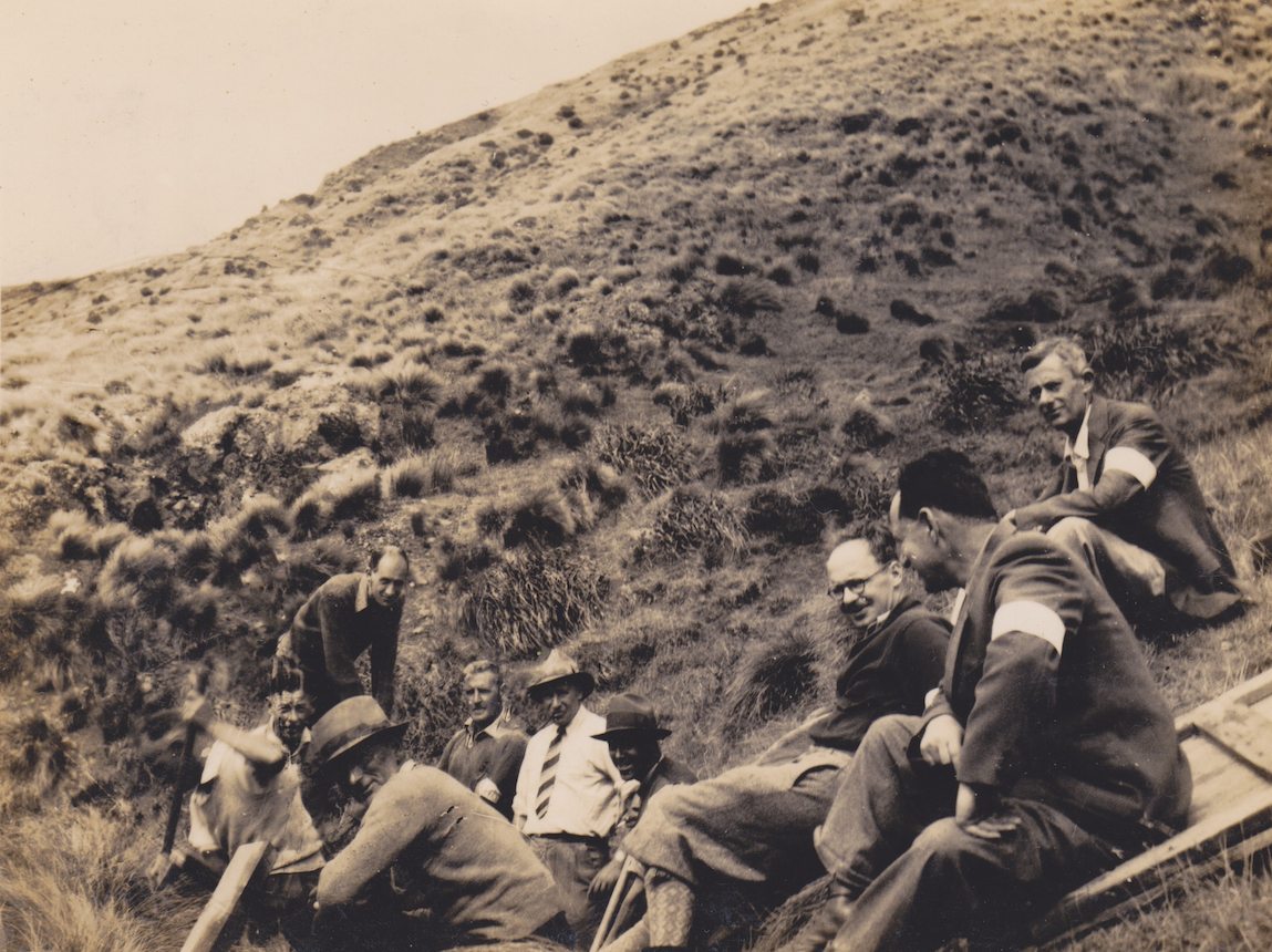 Members of the Makara Battalion, New Zealand Home Guard, take a break in the hills above Ohariu Bay, Makara, 1942. They are, L to R, Fowler, Bridge, Bull, Welsh, Milwood, Hall, Elice, Rhodes (above) and Hertzfield (below). Several of the men are wearing their Home Guard armbands - an example of which, from a member of the Makara Battalion, survives at the National Army Museum Te Mata Toa. Lemuel Lyes Collection.