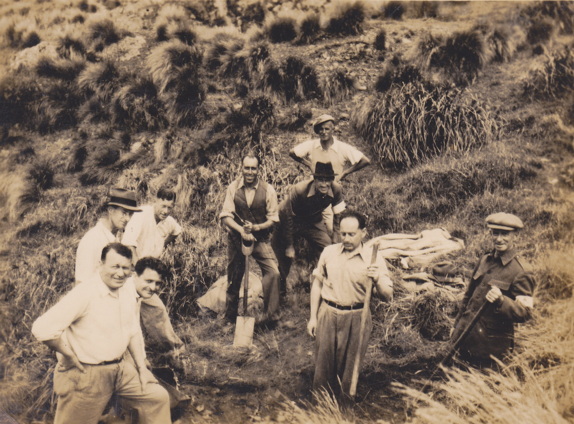 Members of No. 11 Platoon, Makara Battalion, New Zealand Home Guard, digging defensive positions at Ohariu Bay, Makara, 1942. They are, L to R, Fromer(?), Rhodes (back), Lipson (front, Fowler (back), Hall, Yates (back), Bridge (middle), Hertzfield (front) and Pine. Lemuel Lyes Collection.
